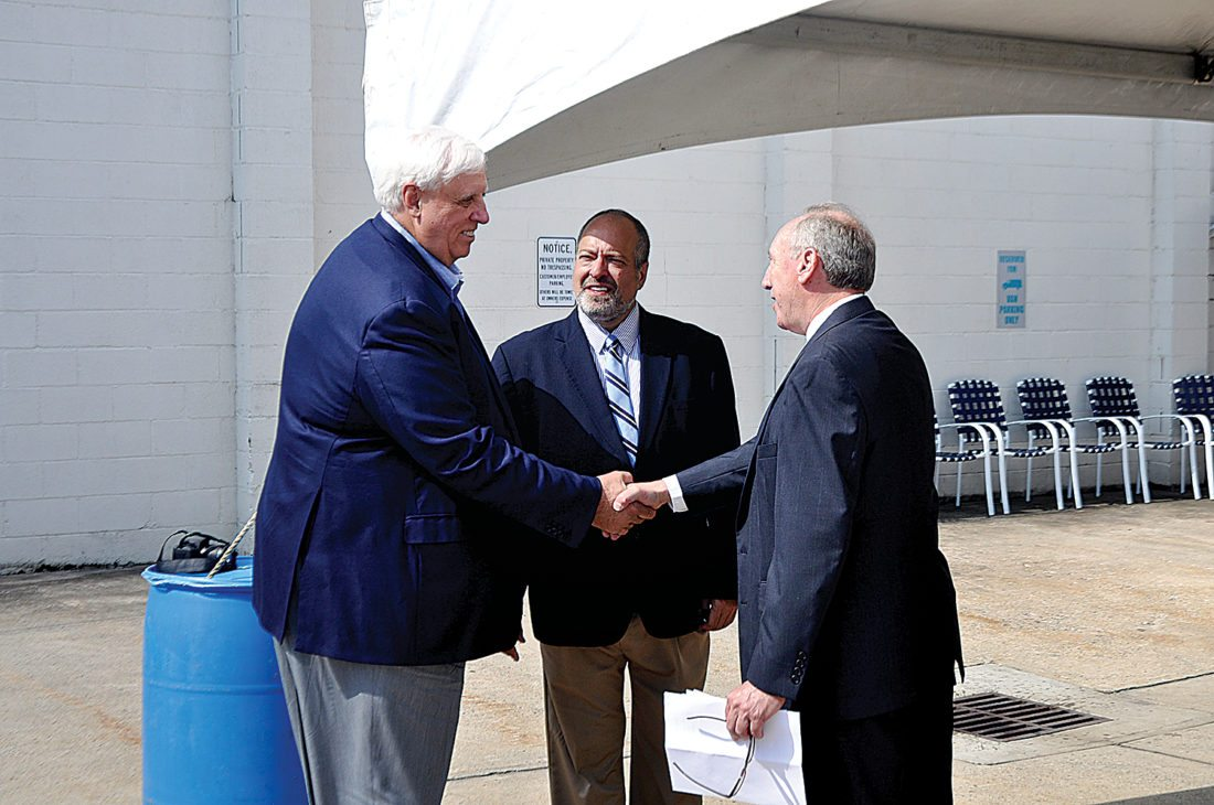 The Inter-Mountain Publisher Steve Herron, right, greets W.Va. Gov. Jim Justice, left, as Justice's Communications Director Butch Antolini looks on. Both Herron and Antolini are natives of Elkins.