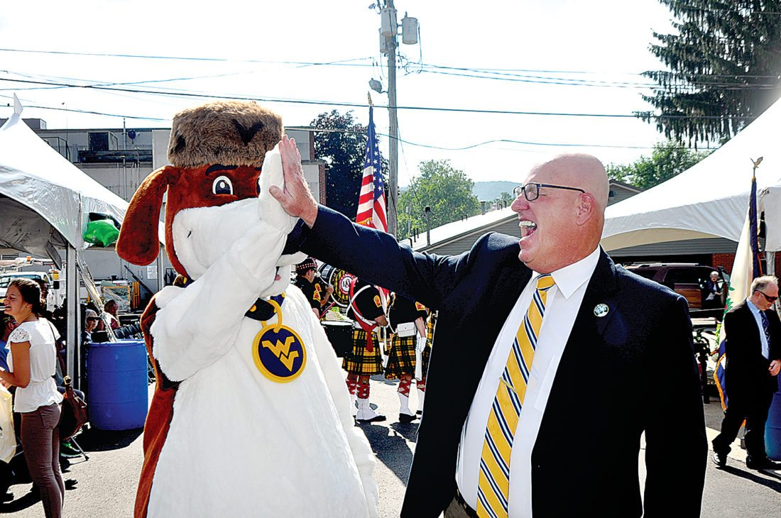 Elkins Mayor Van Broughton, right, give West Virginia University mascot Musket a high five prior to the start of festivities for The Inter-Mountain's 125 Anniversary Celebration on Saturday.