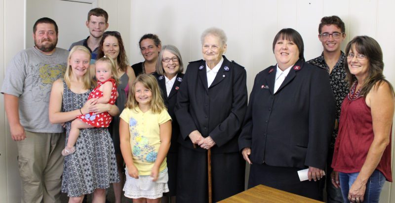 The Inter-Mountain photo by Brooke Binns In honor of Dixie Martin, a lifelong member of Degree of Honor Protective Association, Martin's family makes two legacy donations to the Elkins unit of the Salvation Army on Tuesday. In 1873, the Degree of Honor association was created as a group that would offer a source of friendship and assistance for wives, daughters and mothers of men who were railroad workers. In addition to serving this organization in local, state and national offices, Martin also volunteered on local, state and national levels of the Salvation Army for many years. Members of Martin's family include, front row, Caitlyn Varney, Grace Scott and Annie Martin; second row, Ricky Martin, Amber Varney, Salvation Army member Joy Haines, member Bonnie Wilfong, Captain Denise Stewart and Cathy Varney; and back row, Allen Pritt, Molly Martin and Stephen Martin.