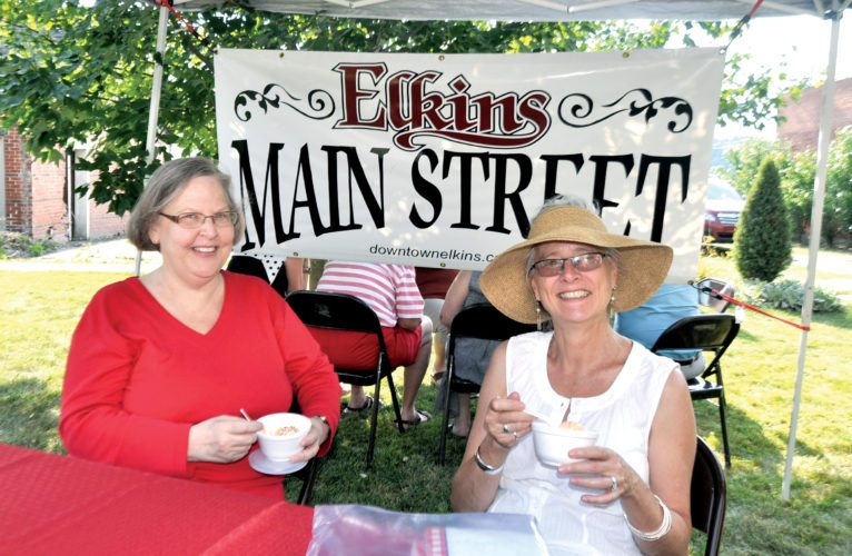 The Inter-Mountain photo by Beth Henry-Vance Naida Vonne Simpson, left, of the Durbin & Greenbrier Valley Railroad, joins Karen Carper, Elkins Main Street executive director, during Thursday's July After Hours Garden Party hosted by Elkins Main Street and the Elkins-Randolph County Chamber of Commerce. It featured ice cream, lawn games and tours of the historic Darden House on Davis Avenue.