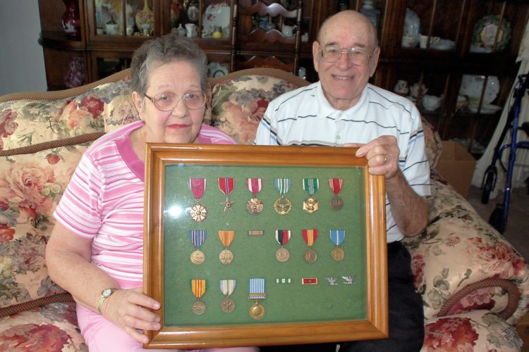 The Inter-Mountain photo by Beth Henry-Vance Col. Herman A. Conrad spent 29 years of active duty with the U.S. Army and served during three wars. The Elkins veteran is shown here with his wife, Betty, and a display of the medals he earned while serving his country.