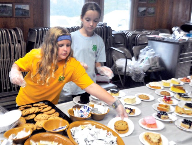 The Inter-Mountain photo by Brooke Binns Randolph County 4-H'ers Madelyn Lambert, left, and Madalynn Ferguson, right, help to keep the dessert table filled with goodies on Thursday evening at the annual Ox Roast offered at Camp Pioneer.