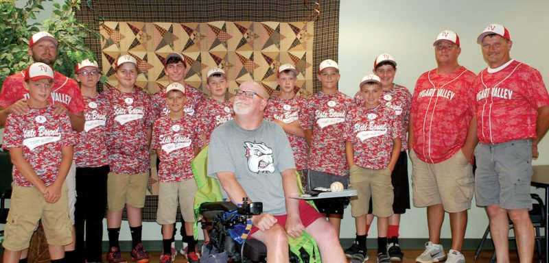The Inter-Mountain photos by Brad Johnson The Tygarts Valley 12-year-old Little League All-Star team and coaches smile after meeting with one of their biggest fans, Stan Gould, at the Elkins Rehabilitation & Care Center in Elkins Thursday evening. The squad presented Gould with a signed game ball and other souvenirs of the state tournament.