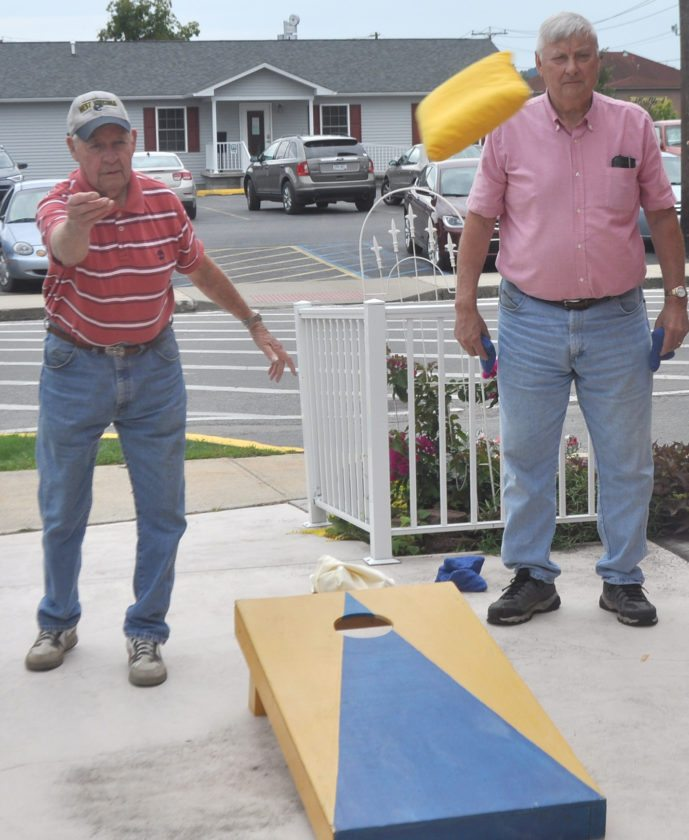 The Inter-Mountain photo by Tim MacVean Jack Lewis, left, of Beverly, pitches bean bags while competing with Harry Canfield, of Elkins, right, in a game of cornhole Thursday afternoon at the Randolph County Senior Center.