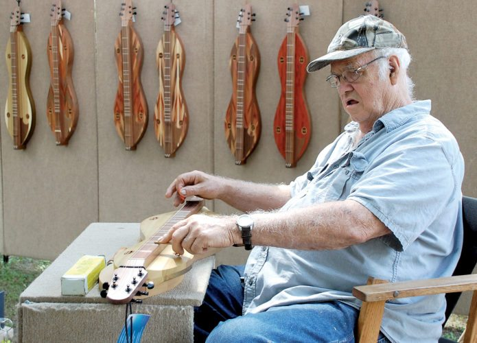 The Inter-Mountain photo by Brad Johnson Eighty-year-old Jim Good, who has built dulcimers for 44 years, is one of the many vendors displaying their wares at the Augusta Festival in Elkins City Park Saturday.