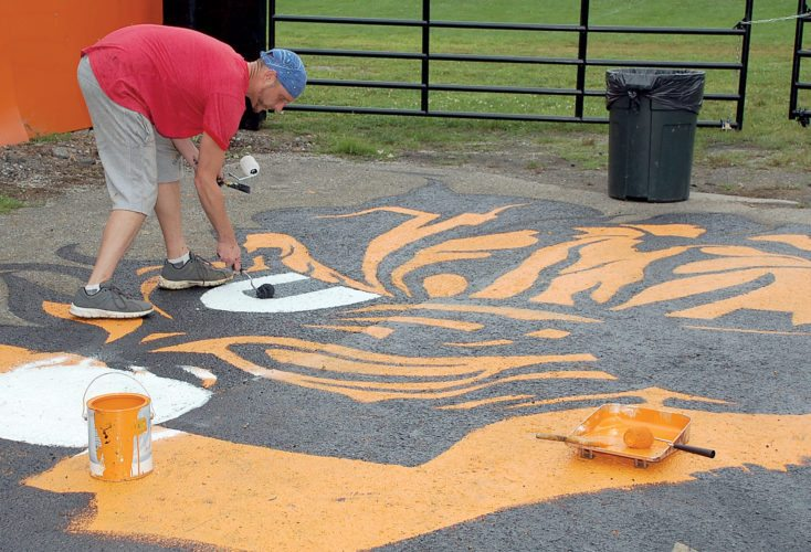 The Inter-Mountain photo by Brad Johnson Chad Winans paints a tiger's head in the parking lot of Wimer Stadium in preparation for the Elkins High School Fighting Tigers' upcoming football season. Winans worked for three evenings to complete his artwork.