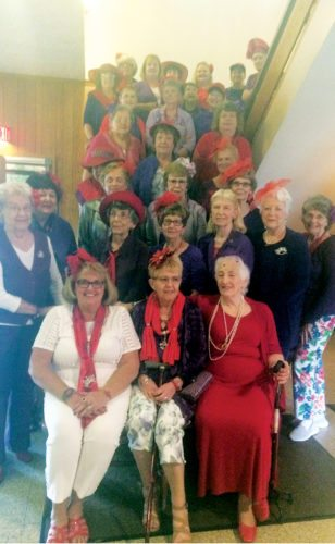 Submitted photo The Elkins Purple Majesties Red Hats gather for a photo during the group's August meeting at Blackwater Falls Lodge Smokehouse Restaurant.