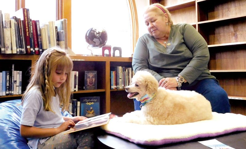 The Inter-Mountain photo by Bayli Helmick Cora Herron, 7, reads to Mountaineer Therapy Dog Brenda Lee with coordinator Barbara Higgins as part of Fun Interacting with Dogs Outloud by the Elkins-Randolph Public Library. FIDO helps children who are new or struggling readers overcome their difficulties by reading to a non-judgmental furry friend. The library's next Dog Days of Summer event will be a hot dog social and open house, from 11 a.m. until 1 p.m. and 4 p.m. to 6 p.m. Aug. 25.
