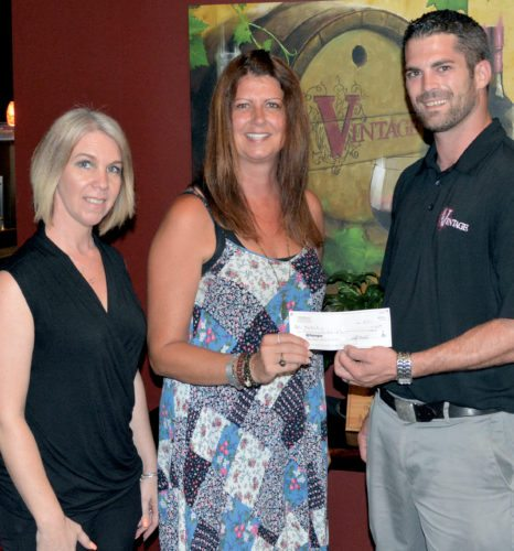 The Inter-Mountain photo by Tim MacVean Vintage Restaurant and Wine Bar owner Scotty Marshall, right, and Kathy Canfield, left, the front-of-house manager, present Elkins Make it Shine Coordinator Melodee Price with a check for $464 that was raised during a June 28 fundraiser. Price said the money will be used for supplies to assist in future painting projects throughout town.