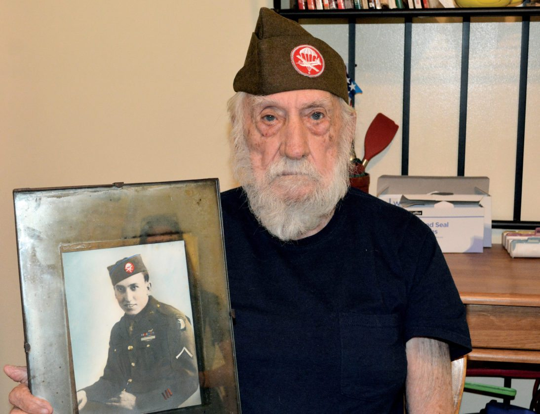 The Inter-Mountain photo by Tim MacVean Robert William 'Buck' Miller, 94, of Elkins, wears the cap he wore during his service in the U.S. Army 101st Airborne Division and holds a picture from his time serving.