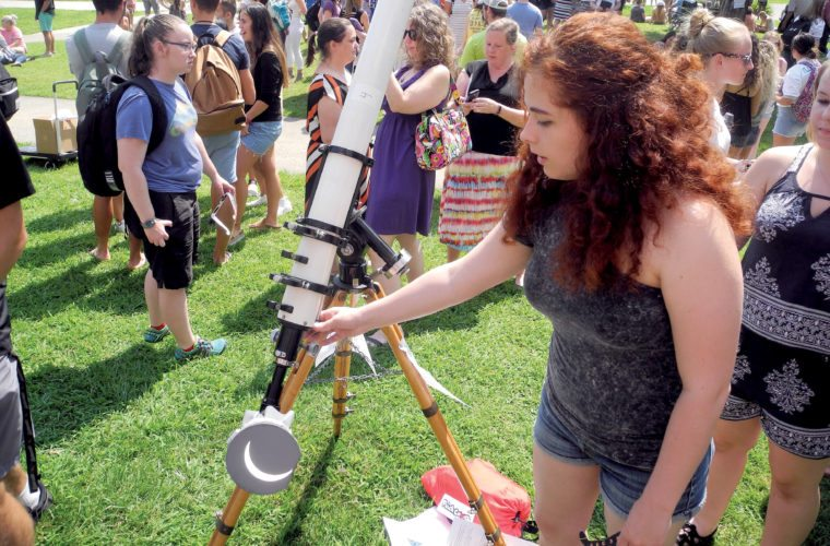 The Inter-Mountain photo by Beth Henry-Vance Kaylee Burdette, a West Virginia Wesleyan College student from Cross Lanes who is involved in the college's SPACE Club and Physics Club, adjusts special projection equipment Monday that shows an image of the partial solar eclipse. The college's viewing party attracted hundreds of students and community members