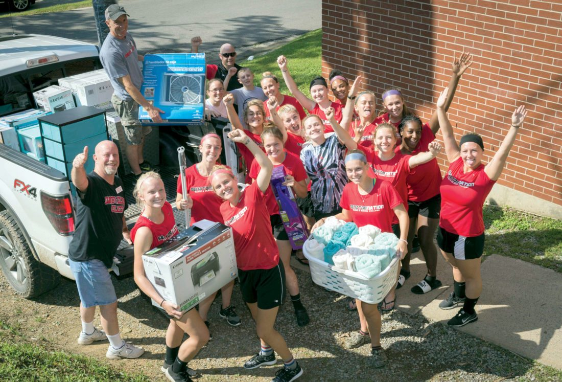 Members of the Davis & Elkins College women's soccer team, along with Professor Brian Moudry, Veterans Upward Bound Director Mark Rosencrance, Director of Athletics Jamie Joss and Head Women's Soccer Coach Megan Gill, unload a new student's belongings and carry them to her room.