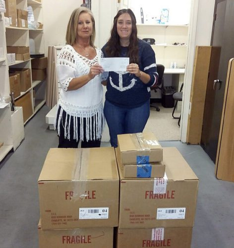 The Inter-Mountain photo by Bayli Helmick Ginger Elmore, store manager of Cato Fashions of Elkins, presents Sara Fincham, Woman's Aid In Crisis victim advocate of Randolph County, with a check for $100 to purchase items needed for residents at the WAIC shelter along with six boxes of clothing.
