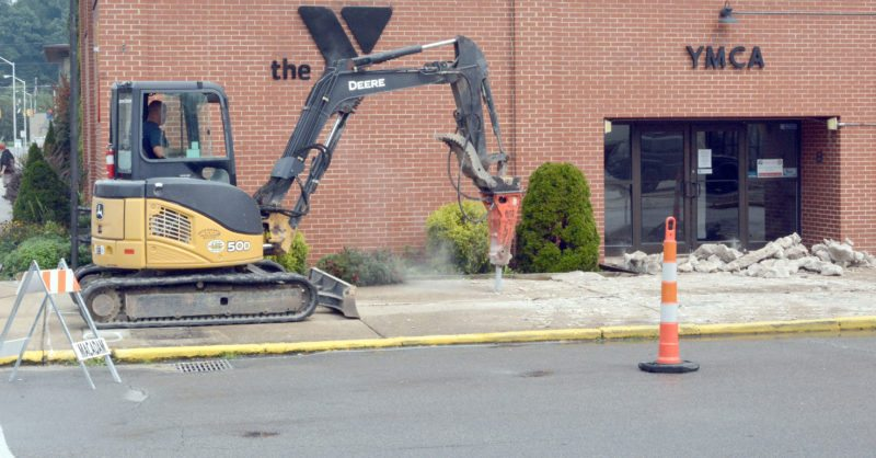 The Inter-Mountain photo by Tim MacVean Neil Smith of Smith Backhoe & Dozer Service tears out the sidewalk in front of the Elkins-Randolph County YMCA Tuesday morning. As part of a beautification project, the YMCA is adding a heated slab of concrete to the sidewalk in front of the building, putting in historical light posts and adding porches, cafe tables, new trash cans and metal grates around trees depicting Elkins landmarks and YMCA sponsors. 'We are hoping to make the curb appeal nice, for downtown Elkins and the YMCA, to try to bring people to enjoy downtown,' YMCA Executive Director Sid Gillispie said Tuesday.