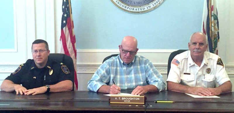 Submitted photo Elkins Mayor Van T. Broughton, center, inks a proclamation Friday joining the city of Elkins with the West Virginia House of Delegates and Gov. Jim Justice in naming the second Saturday of September as 'Heroes Day' to honor firefighters, law enforcement and EMS workers. Also pictured are Elkins Police Chief Glenn Galloway, left, and Elkins Fire Chief Tom Meader.