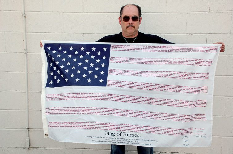 The Inter-Mountain photo by Brad Johnson Stacy Bennett, a 21-year member of the Leading Creek Volunteer Fire Department, displays an American flag listing all the names of the emergency services personnel who gave their lives to save others during the terrorist attacks of Sept. 11, 2001. Bennett has walked through the Mountain State Forest Festival Firemen's Parade carrying the memorial flag.