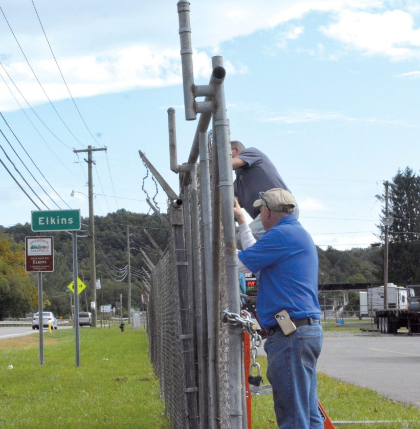 A Department of Highways District 8 crew works to repair a fence that was torn down after a DOH truck was stolen Monday night and driven through the gate.