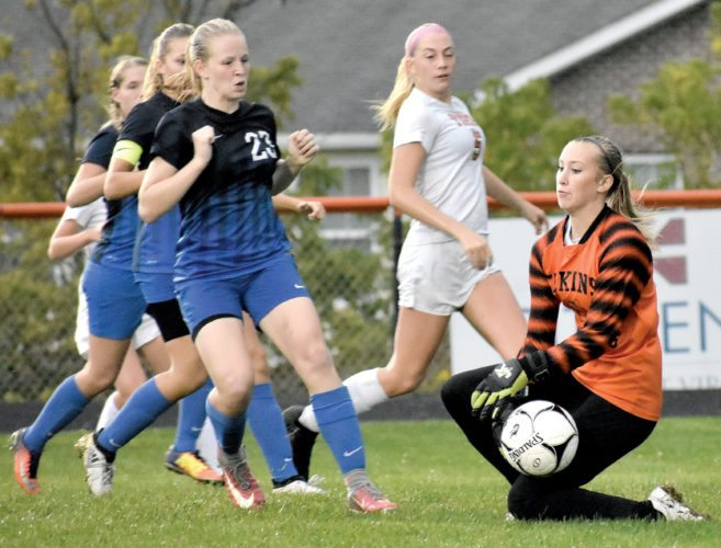 The Inter-Mountain photo by Logan Comer Elkins goalie Taylor Phillips, right, goes to her knees to corral the ball against Fairmont Senior Thursday.