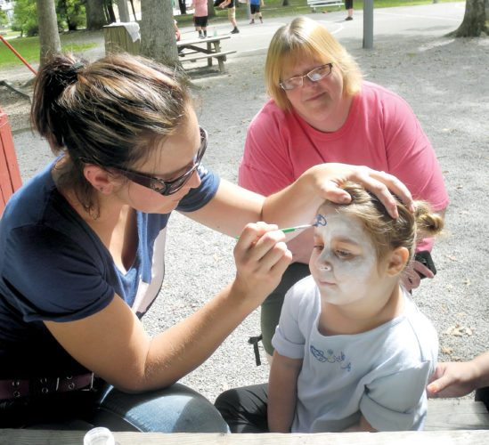 The Inter-Mountain photo by Beth Henry-Vance Khloe Bennett, a Jennings Randolph Elementary School pre-kindergarten student, gets her face painted at Elkins City Park with her aunt, Dawn Bennett, rear, and her mother, Johanna Huffman, not pictured. Face painting, a picnic lunch and parent meeting were part of the 'Back to School Bash' hosted for local students and their families by Randolph County Pre-K.