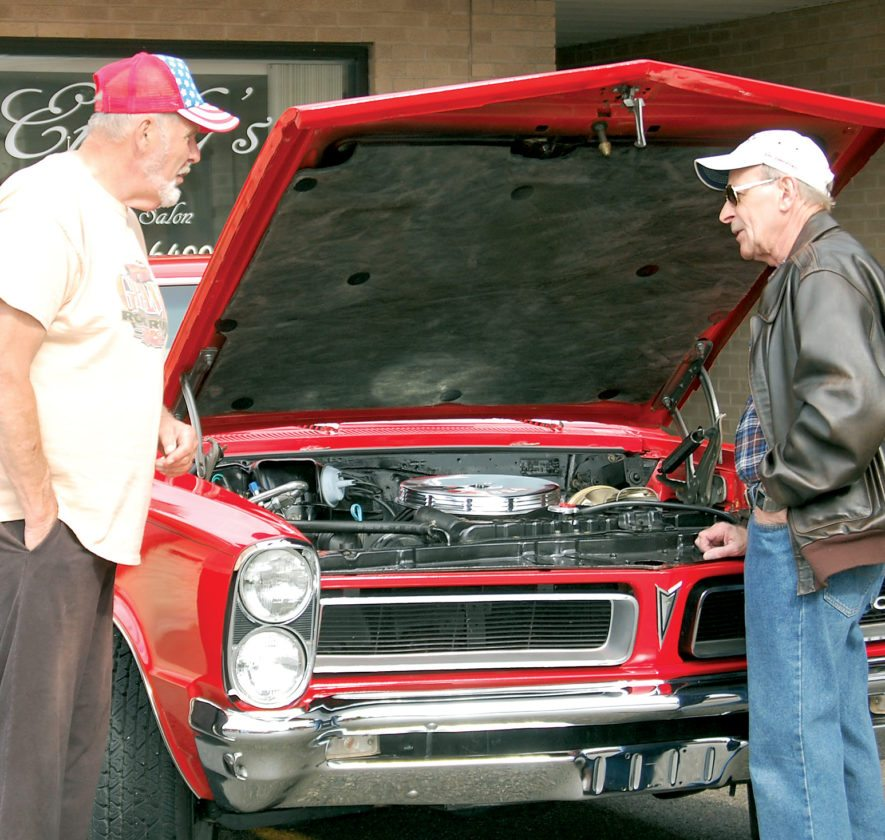 The Inter-Mountain file photo by Tim MacVean Morris Kittle, of Elkins, right, and Jerry Phillips, of Buckhannon, talk about the engine on Kittle's 1965 Pontiac GTO at an Elkins Cruise-In event in the parking lot across from the Elkins Depot Welcome Center.