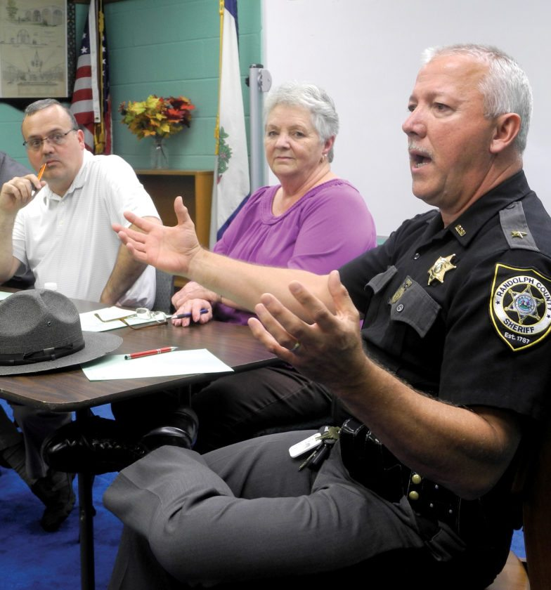 The Inter-Mountain photo by Brad Johnson Randolph County Sheriff Mark Brady, right, speaks at a town hall Tuesday as Randolph County Commissioner Mark Scott, left, and Elkins City Councilwoman Linda Vest look on.