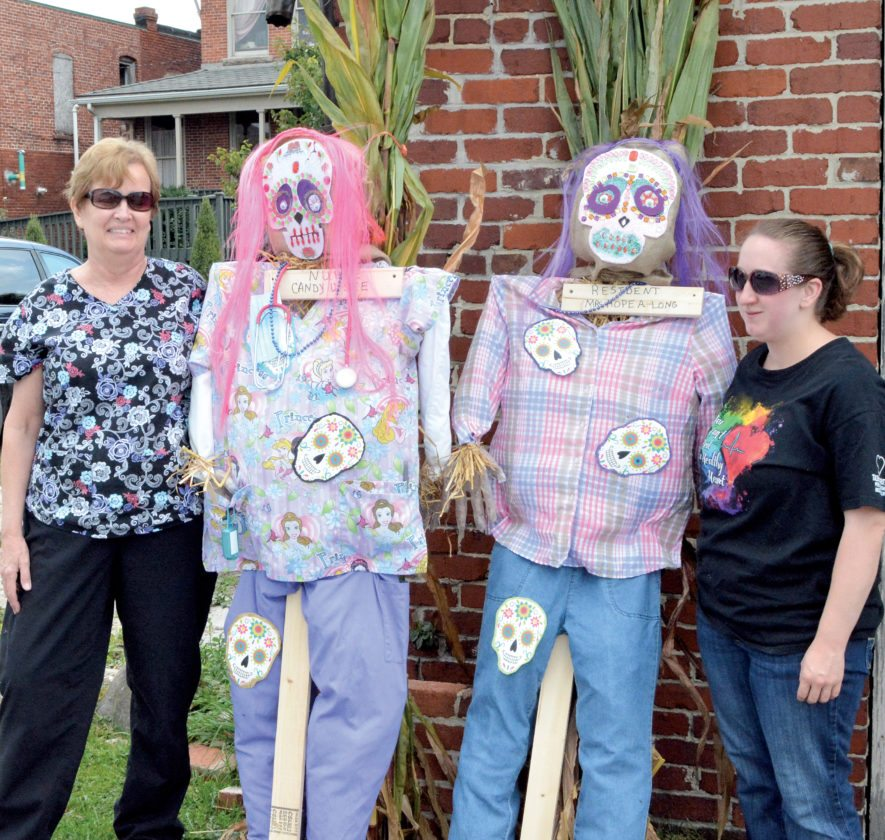 The Inter-Mountain photo by Tim MacVean Valentine's Personal Care Home employees Debbie White, left, and Christy Arbuthnot drop off their scarecrows, 'Nurse Candy U See' and 'Resident Mrs. Hope A Long,' Wednesday afternoon at the Carriage House behind the Darden House. All entries for the third annual Scarecrow Festival will be placed around downtown Elkins Saturday morning.