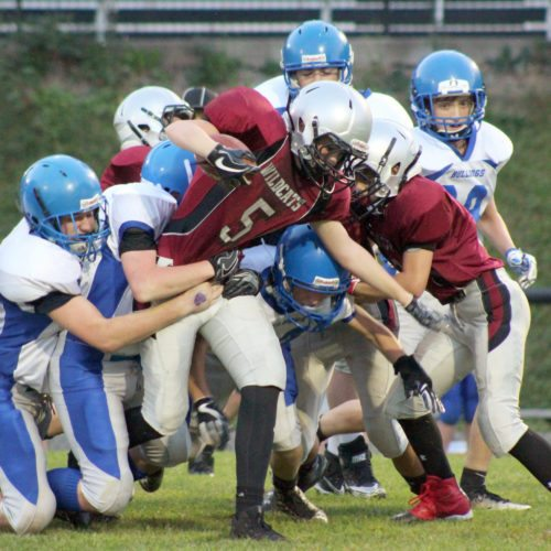 The Inter-Mountain photo by Brittany Hardy Tucker Valley Middle School's Wes Strawderman rips his way up the field carrying along a host of defenders Wednesday night in Parsons. Barbour County won the contest, 34-22.