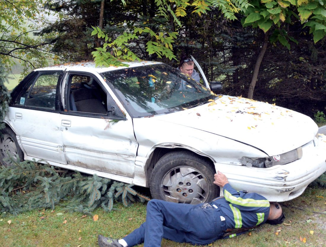 The Inter-Mountain photo by Tim MacVean Staff of Tincher's Towing Service, in Elkins, work to free a vehicle from a group of trees after it was involved in a single-vehicle accident Thursday morning in Beverly. The driver of the vehicle was killed in the accident, officials said.