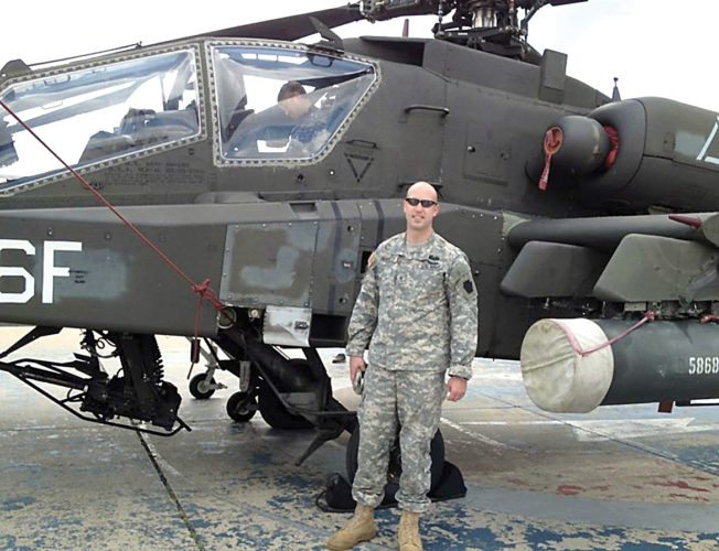 Submitted photo Travis Bennett, a former attack helicopter pilot, stands proudly in front of an AH-64 D Apache Longbow attack helicopter.