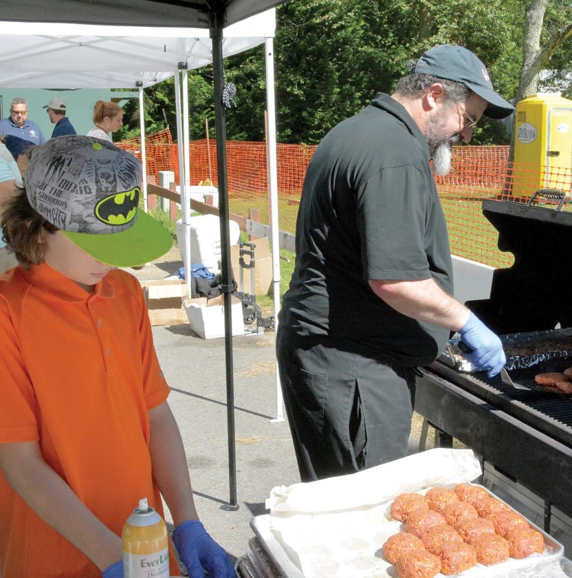The Inter-Mountain photos by Tim MacVean Vintage Restaurant and Wine Bar Executive Chef James DeCarlo, right, receives assistance from his son, James DeCarlo IV, as he makes 'Holy Smokes Burgers,' Saturday afternoon at the 2017 Mountain State Forest Festival Autumn Ales Craft Beer Festival. Also on the Vintage menu were black bean burgers, hummus cups and meatball sliders.