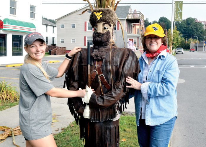 Volunteer Jane Hoxmeier, right, and Davis & Elkins College women's lacrosse player Savannah Stanford pose next to a scarecrow inspired by the West Virginia University Mountaineer mascot.