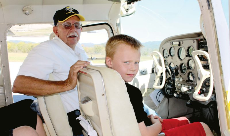 The Inter-Mountain photo by Brooke Binns Isaac Albee takes part in free flights offered by the Elkins Chapter of the Experimental Aircraft Association in Elkins this weekend, as part of a program for local youth. Albee was flown by Richard Judy.