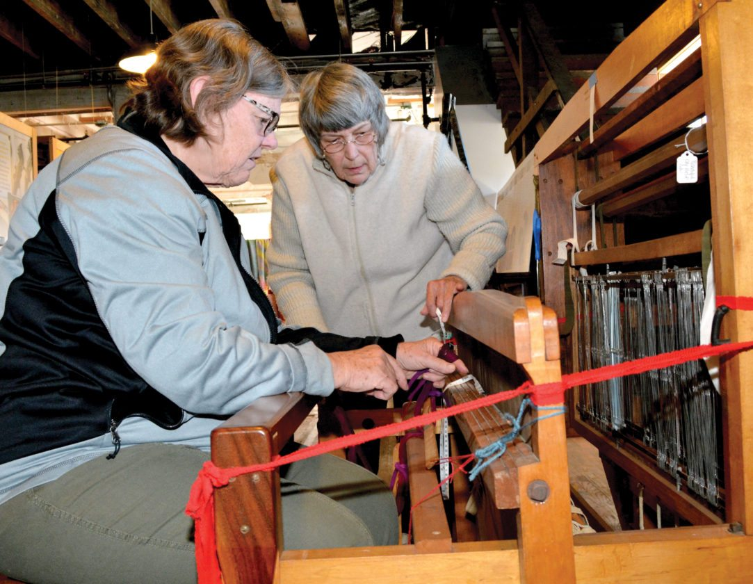 The Inter-Mountain photo by Tim MacVean Joan Pitts, Mountain Weavers Guild treasurer, left, and Vicki Alfano, MWG member, work to place a new warp on a loom Wednesday morning at the Darden Mill, located at 2¢ Railroad Ave., in Elkins. The 81st Mountain State Forest Festival will be open to the public from 9:30 a.m. to 5:30 p.m. today through Saturday. Tickets are also available at the exhibit for a scarf, that will be spun by guild members using alpaca fleece donated by Becky Hill and raffled off Saturday.