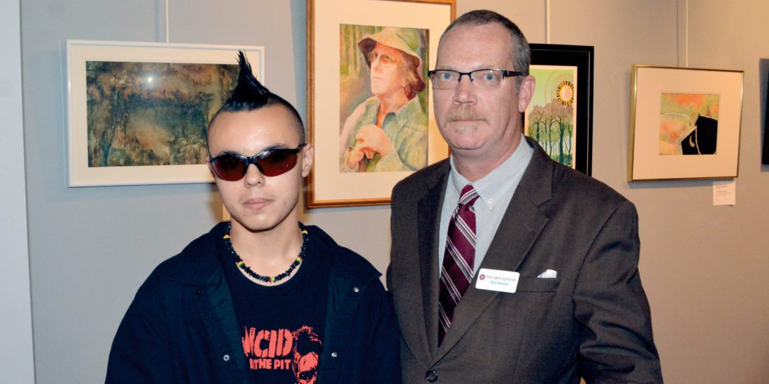 Robert C. Byrd High School 12th grade student Zorian Misner, left, stands with The Arts Center Executive Director Kurt Barkley after receiving the student art exhibit 81st Mountain State Forest Festival Best in Show award Wednesday night.