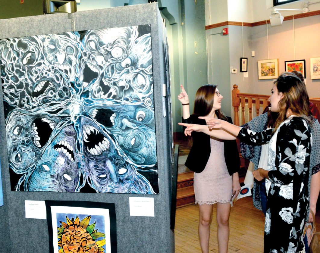 The Inter-Mountain photos by Tim MacVean A group of onlookers admire artwork during the 81st Mountain State Forest Festival annual juried art exhibit Wednesday night at The Arts Center in Elkins. See additional photos from the Forest Festival on pages A3 and A8.