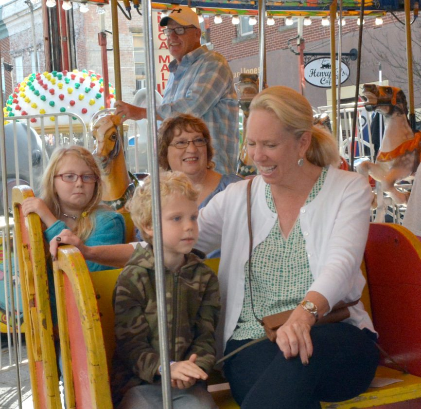 The Inter-Mountain photo by Tim MacVean Erik Martin, 6, and his sister, Anastasia Martin, 9, ride the merry-go-round with donors who worked to raise money that supplied more than 100 free carnival passes to area children. From left are Anastasia Martin, Erik Martin, fundraiser Judy Schoonover Ritchie and fundraiser Michelle Row Williams. Elkins Mayor Van T. Broughton, who helped spearhead the project, is also pictured at back.