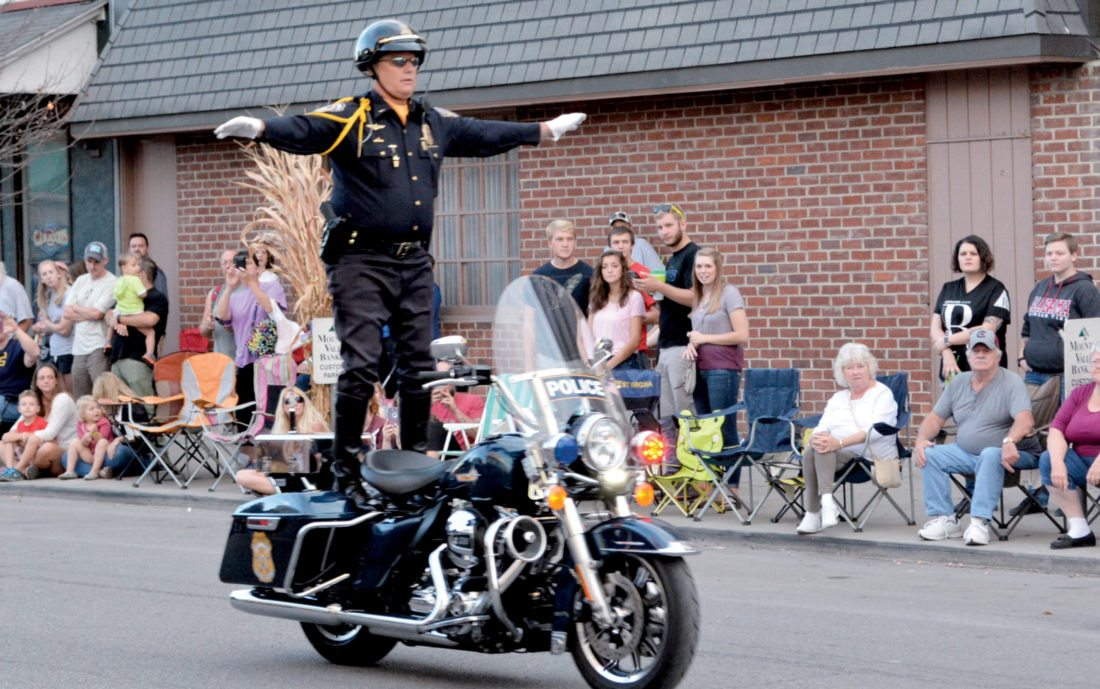 The Inter-Mountain photo by Tim MacVean An Indianapolis Metropolitan Police Motorcycle Drill Team officer stands atop his moving motorcycle during a Mountain State Forest Festival performance Friday evening.