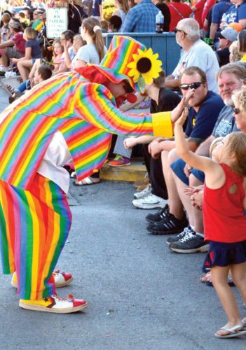 The Inter-Mountain photos by Tim MacVean A clown high-fives a youthful spectator during the Mountain State Forest Festival Grand Feature Parade Saturday afternoon.