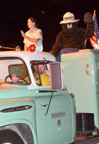 The Inter-Mountain photo by Tim MacVean An antique United States Forest Service fire engine provides the perfect ride for Smokey the Bear as he says 'Only you can prevent forest fires' to patrons of the 81st Mountain State Forest Festival Fireman's Parade Friday night.