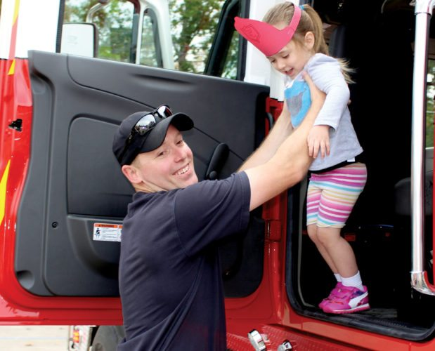 Scott Kennedy, firefighter from the Leading Creek Volunteer Fire Department, helps a young student from Shining Light Pre-School out of a fire engine during a visit to the school on Thursday. Each student received a gift bag filled with pencils, crayons, a fire education coloring book and a firefighter hat in celebration of the U.S. Fire Administration's 2017 Fire Prevention Week.
