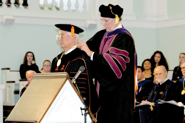 The Inter-Mountain photos by Brooke Binns During Friday's investiture ceremony, Gavin Appleby, chair of West Virginia Wesleyan's Board of Trustees, back, places a medallion on President Joel Thierstein.