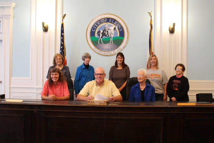 The Inter-Mountain photo by Brooke Binns Elkins Mayor Van Broughton signs a proclamation declaring Oct. 15-21, 2017, as National Friends of Libraries Week in the city. Friends of the Elkins-Randolph County Public Library raise money to help the library have the ability and means to be great. The group works to provide equipment, books, DVDs, special events, support for children's summer reading and much more. Pictured from left in the front row are Laura Hill, Broughton and Virginia Cassells; in the back row are Linda Rudy, Naomi Cassells, Heidi Jeffries, Stephanie Murphy and Linda Daniels.
