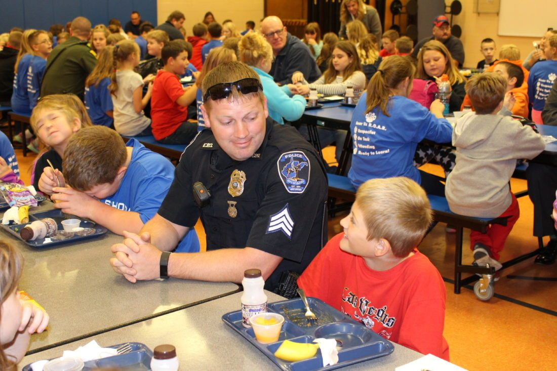 The Inter-Mountain photos by Brooke Binns During his visit for Superhero Day on Tuesday, Cpl. M.J. Sigley of the Elkins Police Department, left, jokes with Gunner Binns, right, a third-grade student at North Elementary School in Elkins.