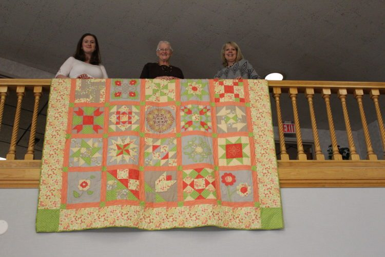 The Inter-Mountain photo by Brooke Binns Volunteers show off a handmade quilt that will be auctioned off during Saturday's United Way auction at the First United Methodist Church in Elkins. From left are United Way Executive Director JoBeth Johnston, Elkins Sewing Center Owner Sue Pifer and President of United Way's Board of Directors Kathy Leombruno. Community members Diana Kerr and Patsy Turner assisted in piecing together the quilt. Materials were donated by the Elkins Sewing Center, which has assisted in the project for nearly 30 years, Pifer said.