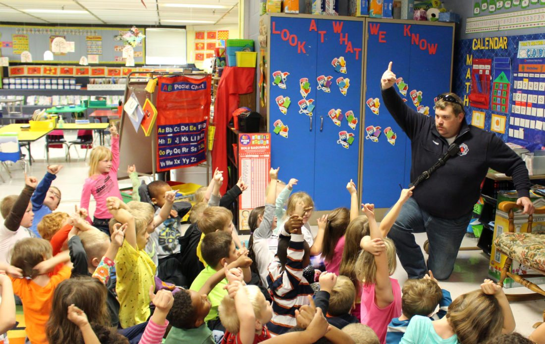 The Inter-Mountain photo by Brooke Binns Kindergarten students at Jennings Randolph Elementary School raise their pinkie fingers Wednesday with Bryan Warner of the Elkins Fire Department to promise they will check the smoke detectors in their homes twice a year with the help of their parents.