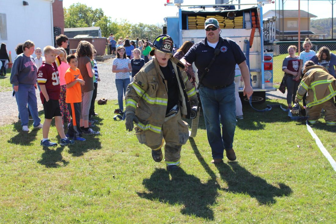 The Inter-Mountain photo by Brooke Binns Bryan Warner of the Elkins Fire Department assists Alexx, a sixth-grade student at Elkins Middle School, in a firefighter relay race this week. Students challenged one another to see who could equip themselves in turnout gear and carry fire equipment the fastest. EMS Assistant Principal Eric Lucas said more than 450 students took part in the nine-weeks reward activity for good behavior.
