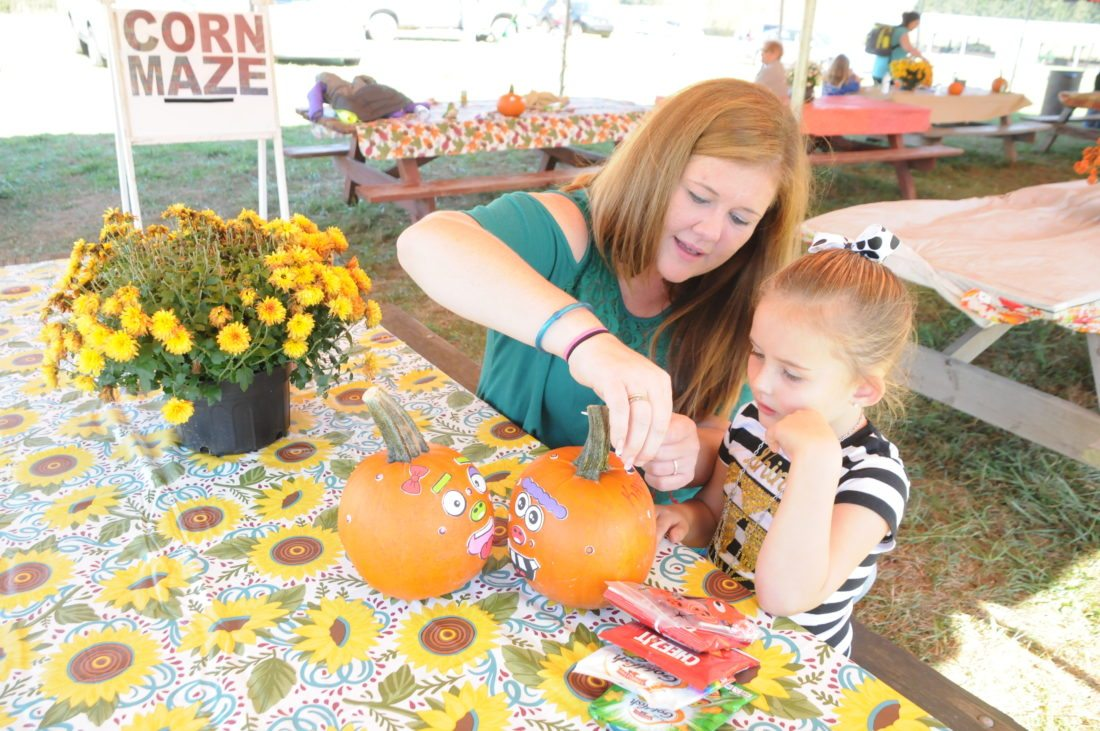 The Inter-Mountain photo by Beth Henry-Vance Kaytlann Richards, a preschool student from George Ward Elementary School, decorates pumpkins Friday with help from her mother, Jessica Sampson. All Randolph County preschoolers were invited to the Randolph County Fair Corn Maze & Pumpkin Patch near Beverly as part of a fall field trip sponsored by North Central West Virginia Head Start.