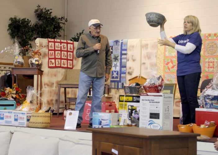 The Inter-Mountain photo by Brooke Binns Many people gave back to area communities by taking part in the Randolph County United Way Auction this weekend. Randolph County United Way Board of Directors President Kathy Leombruno, right, displays a piece of pottery crafted by Scottie Wiest, and Ron Phillips, left, prepares to begin auctioning off the item. The piece was sold for $55. All proceeds from the auction will be dispersed to 20 nonprofit organizations in the county.