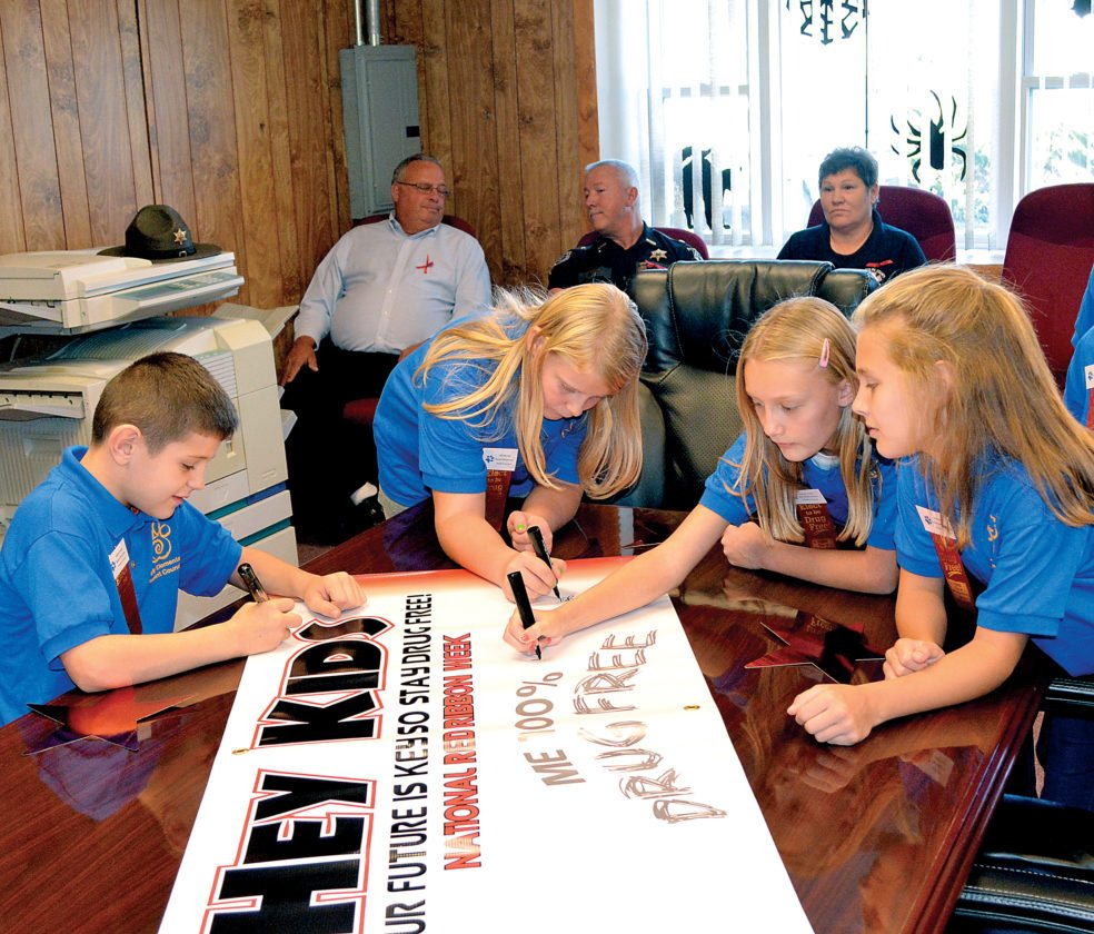 The Inter-Mountain photo by Tim MacVean Students from Beverly Elementary School sign an anti-drug banner at Beverly Town Hall as part of National Red Ribbon Week, being observed this week in the town of Beverly. The banner will hang in the town square, and a proclamation was also inked by Beverly Mayor Cindy Karelis. Members of numerous law enforcement agencies, first responder agencies and governmental agencies also attended the event.