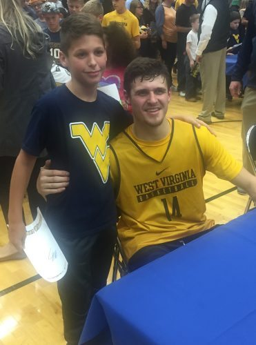 T-L Photo/SETH STASKEY  WEST VIRGINIA basketball player Chase Harler, who is a Wheeling CC grad, poses with Hayden Mueller, who is a sixth grader at St. Michael's in Wheeling.